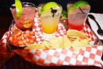A variety of mixed drinks with chips and salsa.