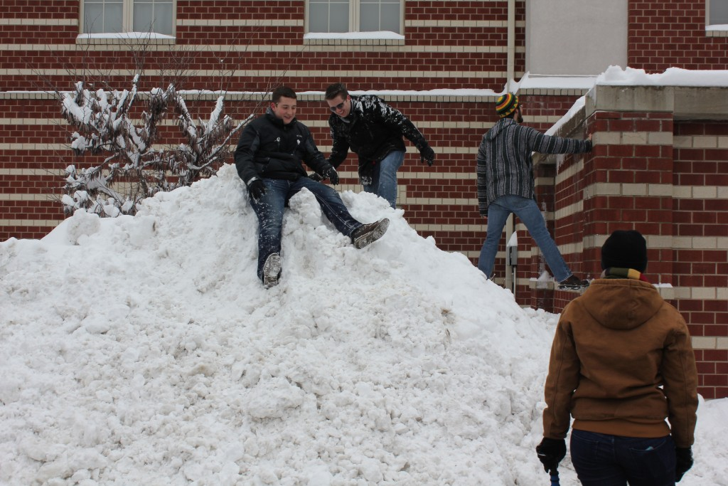 UofL students using the plowed snow as a mini hill. Photo by Samantha Crowder.