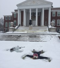 Students Adri Barnes and Heather Griffith make snow angels by Grawemeyer Hall.Photo by Ali Davis