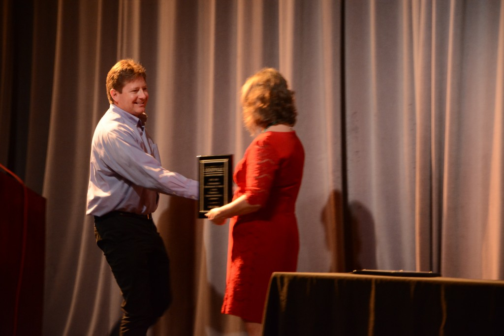 Rick Taylor shakes hands with Dr. Kimberly Kempf-Leonard before accepting the award for Outstanding Performance in the Technical/Paraprofessional Category.   Photo by Rachel Knue.