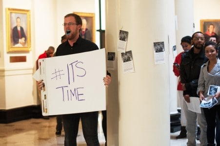 A student protests inside Grawemeyer Hall.